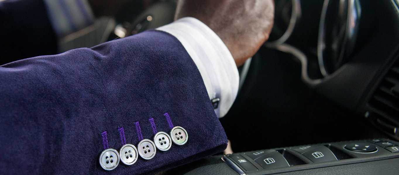 Men's purple tailored suit showing buttons and cuff detail in car